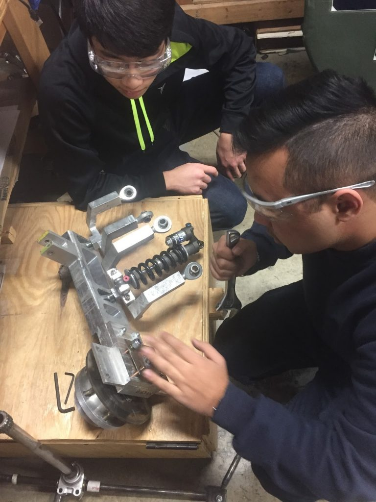 Picture: Solar Car members Adeesh Shrestha and Tommy Tsuchiya work on taking the old suspension system apart.